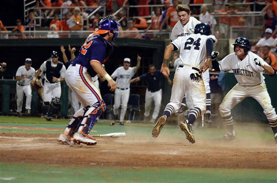 Connecticut's L.J. Mazzilli (24) of Greenwich scores the winning run to defeat Clemson 7-6 during an NCAA college baseball regional tournament game against Clemson at Doug Kingsmore Stadium Sunday, June 5, 2011, in Clemson, S.C. (AP Photo/ Richard Shiro) Photo: RICHARD SHIRO, AP / (2011) Richard Shiro