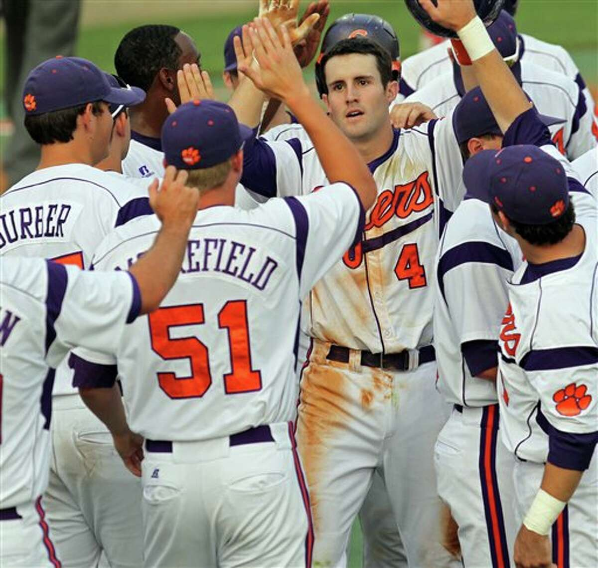 Clemson's John Hinson (4) gets high-fives from his teammates after hitting a three-run home run during an NCAA college baseball tournament game against Sacred Heart at Doug Kingsmore Stadium in Clemson, S.C., Friday, June 3, 2011. (AP Photo/Anderson Independent-Mail, Mark Crammer)