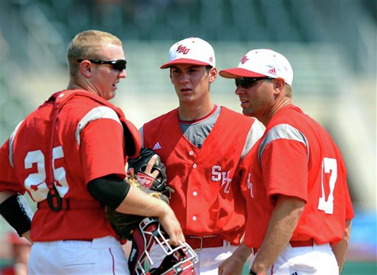 Sacred Heart's pitching coach Wayne Mazzoni, right, talks with pitcher Nick Leiningen, center, and catcher Derick Horn (25) at the mound during an NCAA Clemson regional college baseball game against Connecticut at Doug Kingsmore Stadium in Clemson, S.C. Saturday, June 4, 2011. (AP Photo/ Richard Shiro)