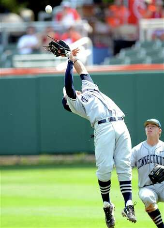 Connecticut second baseman L.J. Mazzilli, left, makes a catch against Sacred Heart during an NCAA Clemson regional college baseball game at Doug Kingsmore Stadium in Clemson, S.C. Saturday, June 4, 2011. (AP Photo/ Richard Shiro) Photo: AP