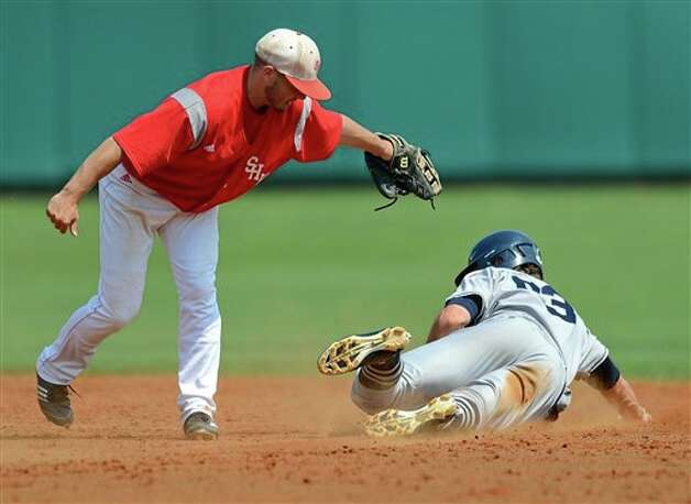 Connecticut's John Andreoli slides under the tag of Sacred Heart shortstop John Murphy during an NCAA Clemson regional college baseball game at Doug Kingsmore Stadium in Clemson, S.C. Saturday, June 4, 2011. (AP Photo/ Richard Shiro) Photo: AP