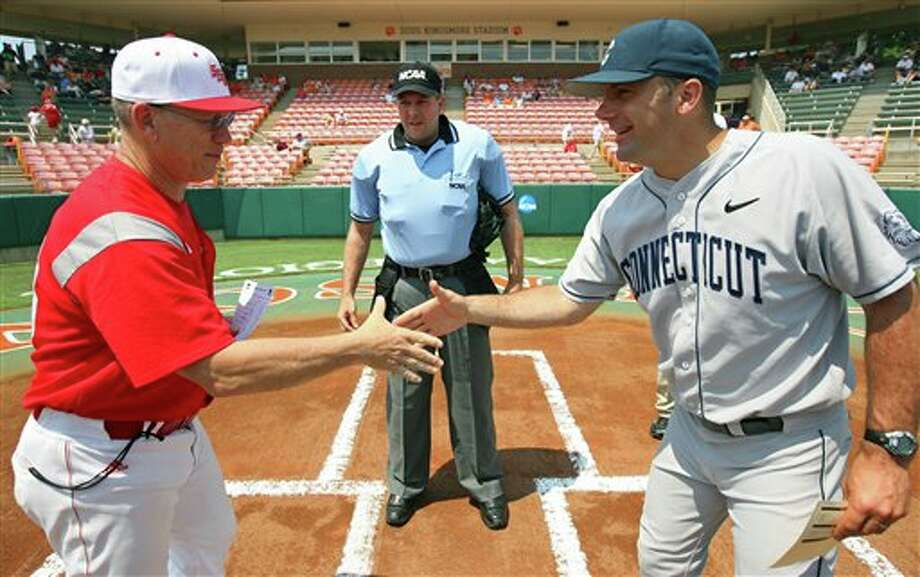 Home plate umpire Don Goller, center, watches as Sacred Heart coach Nick Giaquinto, left, and Connecticut coach Jim Penders shake hands before their NCAA regional tournament college baseball game at Doug Kingsmore Stadium in Clemson, S.C. on Saturday, June 4, 2011. Connecticut won the game 13-3  to eliminate Sacred Heart from the tournament. (AP Photo/Anderson Independent-Mail, Mark Crammer) Photo: AP