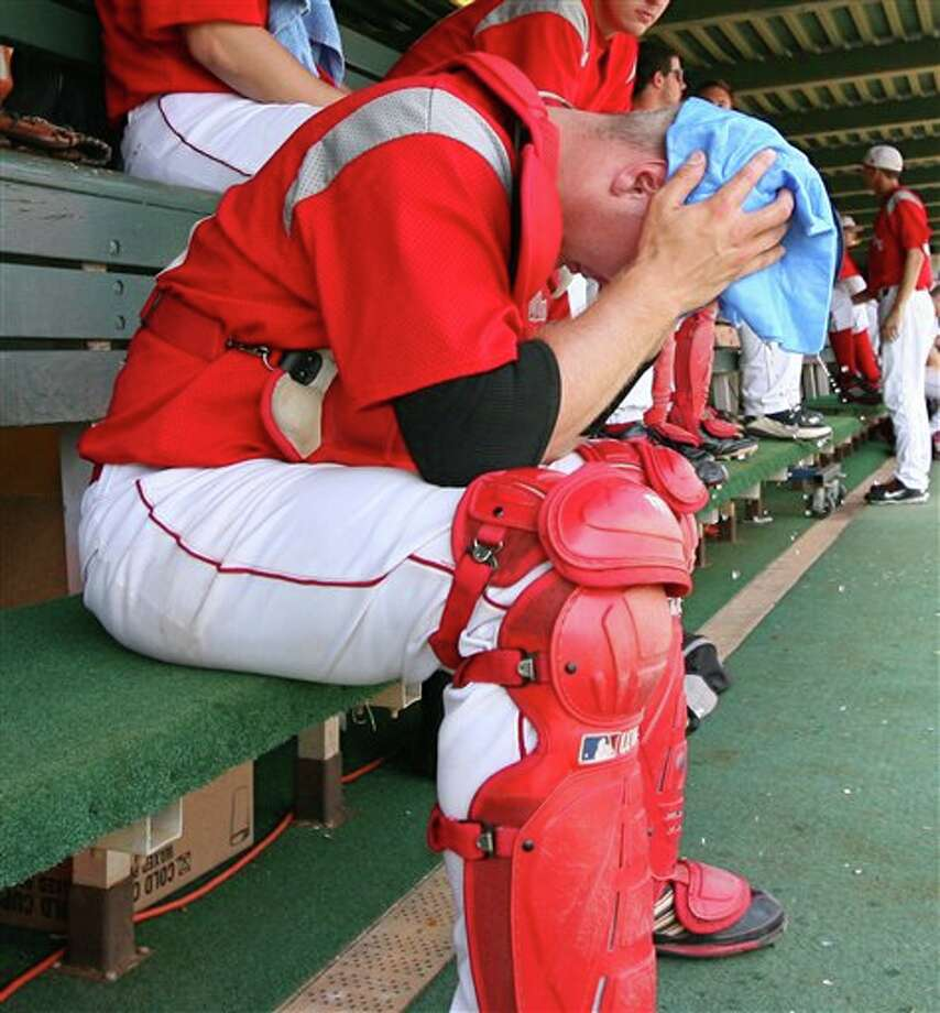 Sacred Heart catcher Derick Horn wraps a wet towel over his head to cool off in the dugout during an NCAA regional tournament college baseball game against Connecticut at Doug Kingsmore Stadium in Clemson, S.C. on Saturday, June 4, 2011. Connecticut won the game 13-3  to eliminate Sacred Heart from the tournament. (AP Photo/Anderson Independent-Mail, Mark Crammer) Photo: AP
