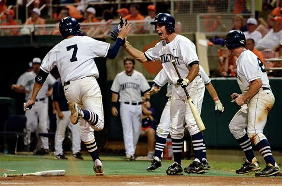 Connecticut's Nick Ahmed (7) high fives Billy Ferriter (right)  after scoring a go ahead run in the eighth inning during an NCAA college baseball regional tournament game against Clemson at Doug Kingsmore Stadium Sunday, June 5, 2011, in Clemson, S.C. (AP Photo/ Richard Shiro) Photo: AP