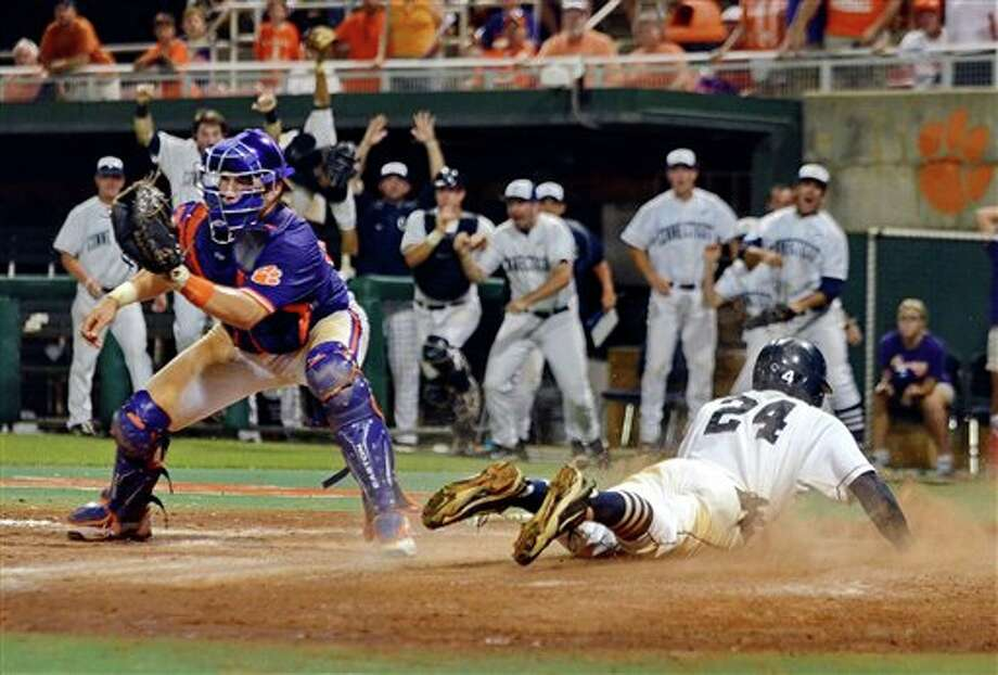 Connecticut's  L.J. Mazzilli (24) scores the winning run to defeat Clemson 7-6 during an NCAA college baseball regional tournament game at Doug Kingsmore Stadium Sunday, June 5, 2011, in Clemson, S.C. (AP Photo/ Richard Shiro) Photo: AP