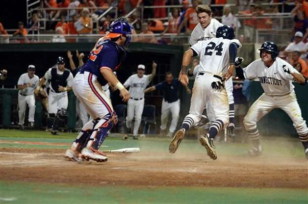 Connecticut's L.J. Mazzill i(24) scores the winning run to defeat Clemson 7-6 during an NCAA college baseball regional tournament game against Clemson at Doug Kingsmore Stadium Sunday, June 5, 2011, in Clemson, S.C. (AP Photo/ Richard Shiro) Photo: AP