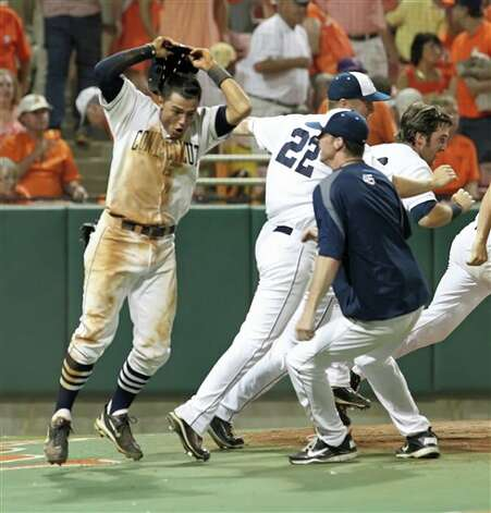 L.J. Mazzilli, left, leaps at home plate after scoring the winning run in the bottom of the ninth in Connecticut's 7-6 win over Clemson during their NCAA regional tournament baseball game on Sunday, June 5, 2011 in Clemson, S.C.  (AP Photo/Anderson Independent-Mail, Mark Crammer) Photo: AP