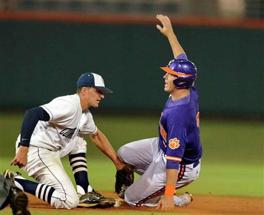 Clemson's Jeff Schaus (right) slides safely under the tag of Connecticut shortstop Nick Ahmed during an NCAA college baseball regional tournament game at Doug Kingsmore Stadium Sunday, June 5, 2011, in Clemson, S.C. (AP Photo/ Richard Shiro) Photo: AP
