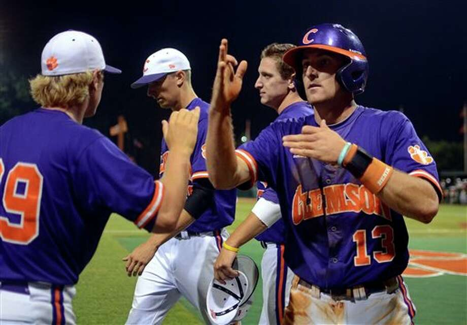Clemson's Brad Miller (13) celebrates a score with David Haselden during an NCAA college baseball regional tournament game against Connecticut at Doug Kingsmore Stadium Sunday, June 5, 2011, in Clemson, S.C. (AP Photo/ Richard Shiro) Photo: AP