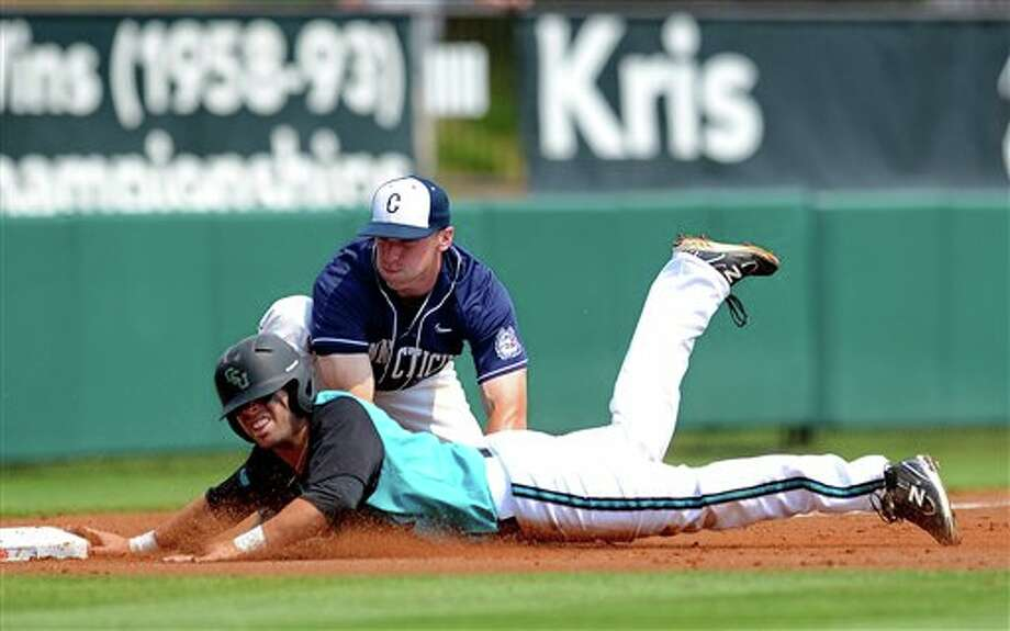 Connecticut third baseman Ryan Fulle,  back, tags Coastal Carolina's Kieth Hardwick out at third base during an NCAA college baseball regional tournament game at Doug Kingsmore Stadium Sunday, June 5, 2011, in Clemson, S.C. (AP Photo/ Richard Shiro) Photo: AP