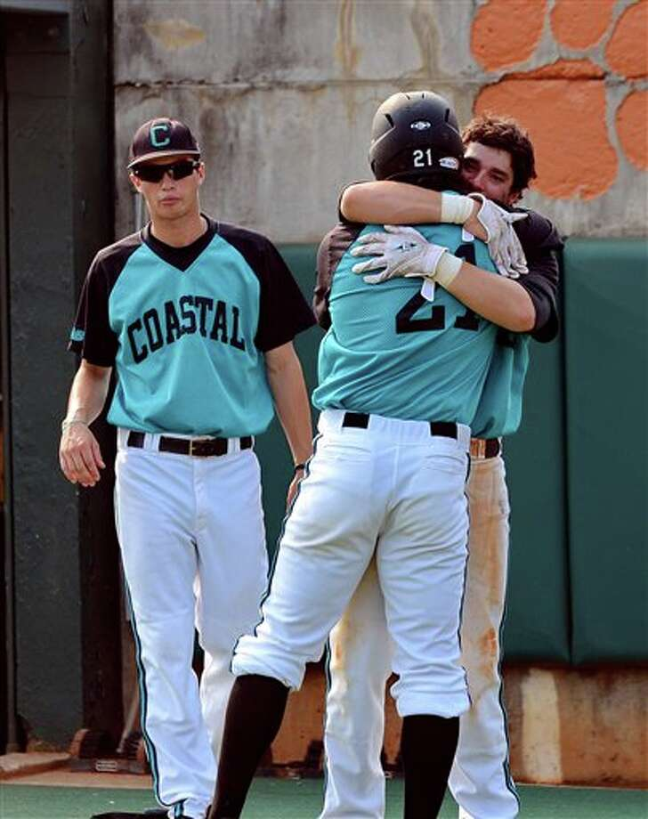 Coastal Carolina's Rich Witten (21)  is hugged by Kieth Hardwick after their 12-6 loss to Connecticut during an NCAA college baseball regional tournament game at Doug Kingsmore Stadium Sunday, June 5, 2011, in Clemson, (AP Photo/ Richard Shiro) Photo: AP