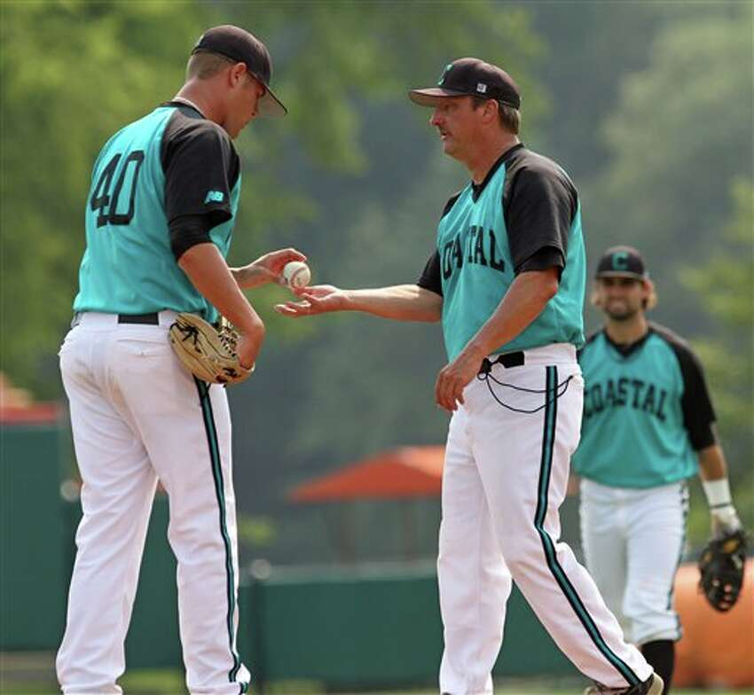 Coastal Carolina pitcher Matt Laney, left, hands the ball to head coach Gary Gilmore after giving up a bases-loaded walk to the only batter he faced in the sixth inning of an NCAA regional tournament baseball game against Connecticut on Sunday, June 5, 2011 in Clemson, S.C. Connecticut won, 12-6, to eliminate Coastal from the tournament. (AP Photo/Anderson Independent-Mail, Mark Crammer)