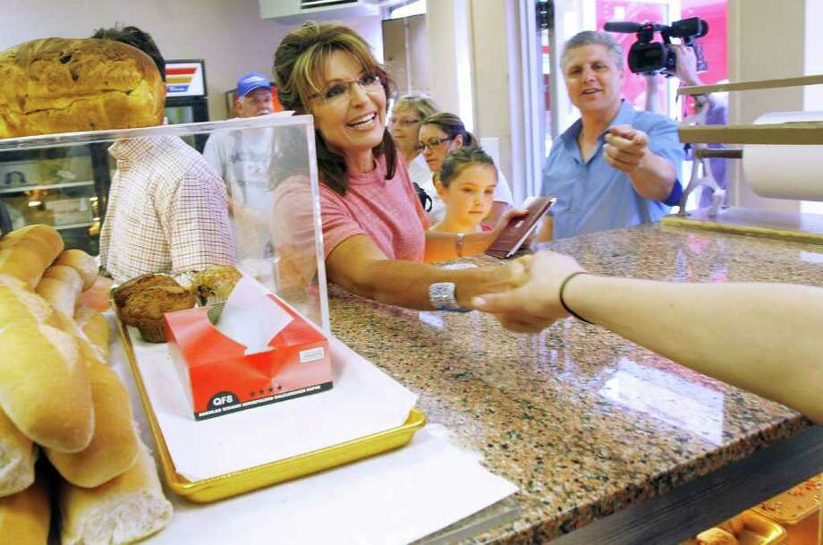 Dino Di Fronzo, right, introduces former Alaska Gov. Sarah Palin to an employee at A. Parziale & Sons Italian bakery as she tours Boston's North End neighborhood, Thursday, June 2, 2011. Photo: Steven Senne, AP / AP