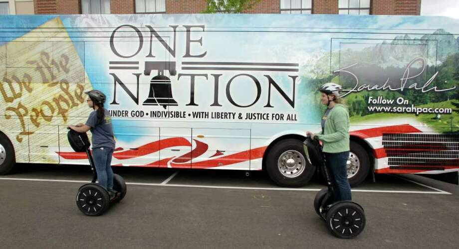 Two women on Segway scooters roll past former Alaska Gov. Sarah Palin's bus in Portsmouth, N.H., Thursday June 2, 2011.  Palin has been visiting East coast cities this past week. Photo: Charles Krupa, AP / AP
