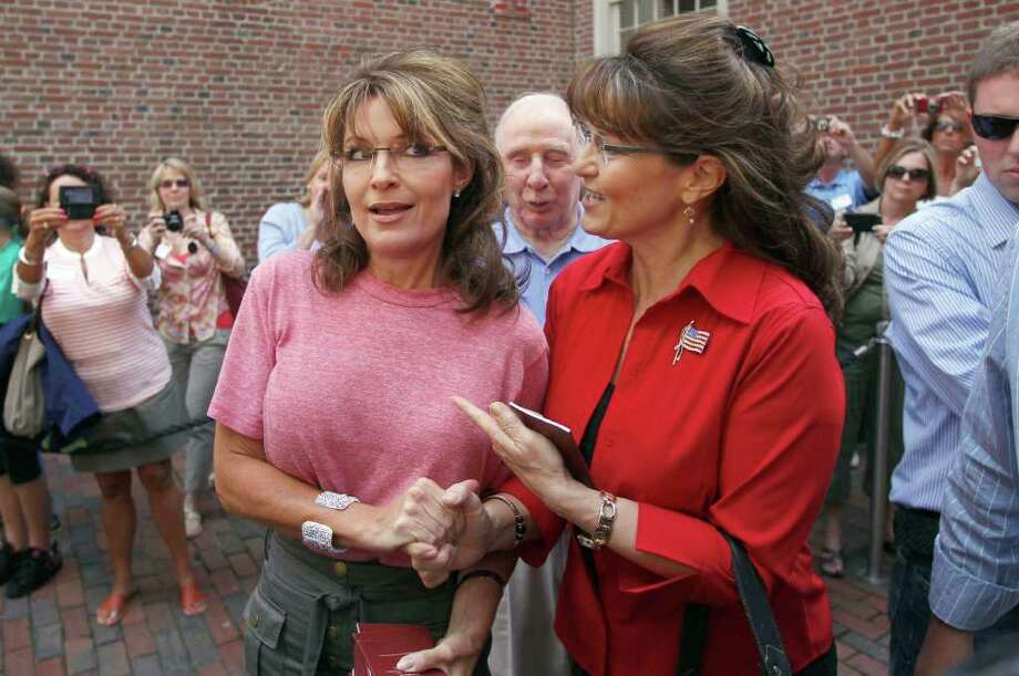 Former Alaska Gov. Sarah Palin, left, poses with celebrity look-alike impersonator Cecilia Thompson during a tour of Boston's North End neighborhood, Thursday, June 2, 2011. Palin's father Chuck Heath is at center. Photo: Steven Senne, AP / AP