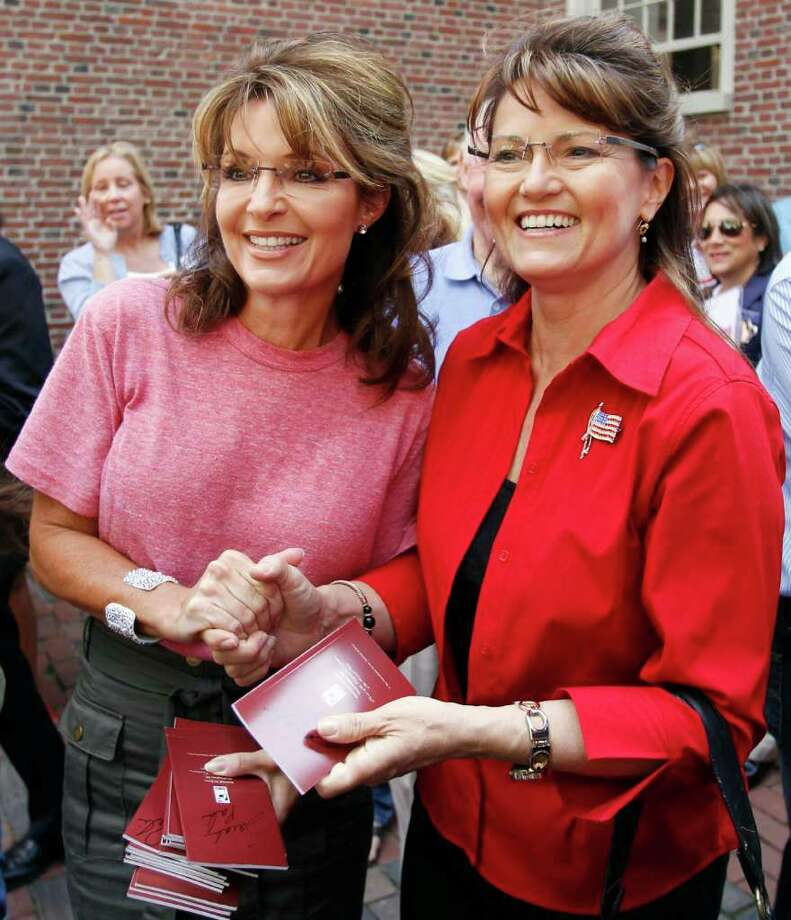 Former Alaska Gov. Sarah Palin, left, poses with celebrity look-alike impersonator Cecilia Thompson during a tour of Boston's North End neighborhood, Thursday, June 2, 2011. Photo: Steven Senne, AP / AP