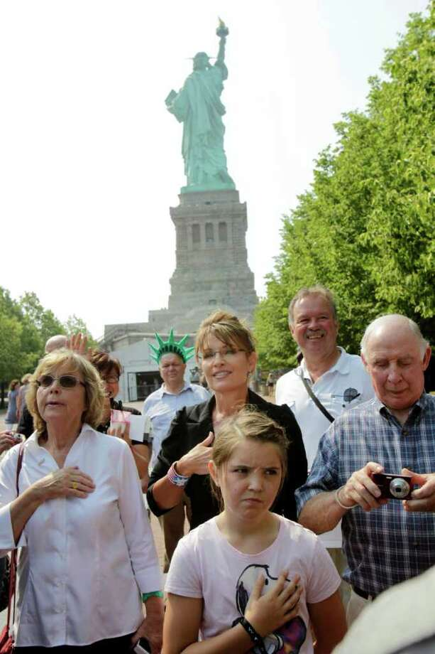 "Sarah Palin, center, her daughter Piper Palin, front, and her parents, Sally Heath, left, and Chuck Heath, right, pause while visting Liberty Island as a band plays ""The Star-Spangled Banner"" in New York, Wednesday, June 1, 2011. Photo: Seth Wenig, AP / AP"