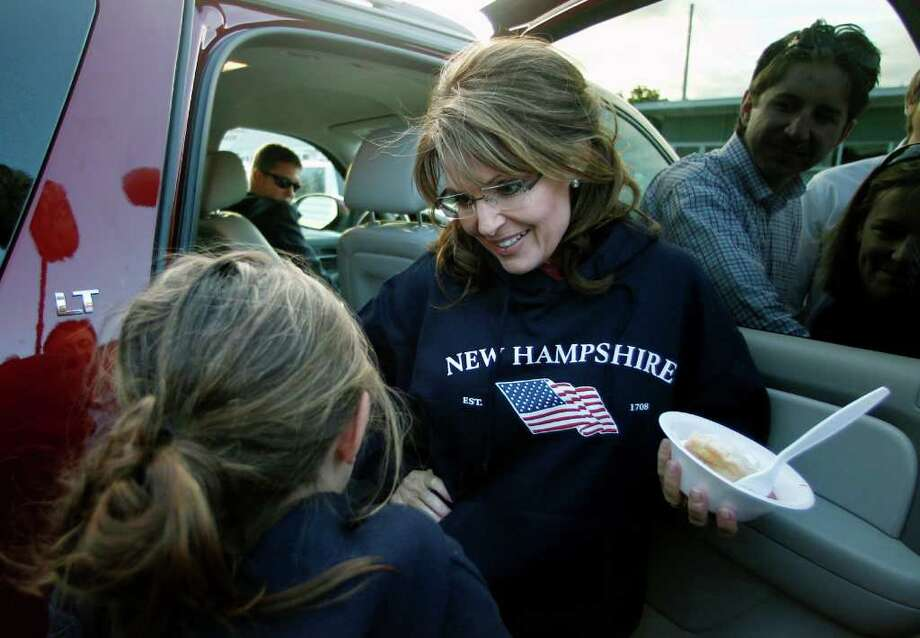 Former Alaska Gov. Sarah Palin listens to her daughter Piper as she prepares to leave a clambake with a bowl of strawberry shortcake in hand in Seabrook, N.H., Thursday, June 2, 2011. Photo: Charles Krupa, AP / AP