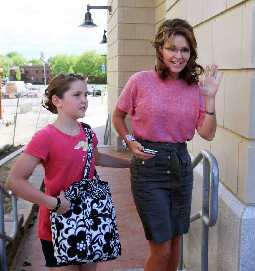 Former Alaska Gov. Sarah Palin and her daughter Piper, leave out of the back door of her hotel in Portsmouth, N.H., Thursday, June 2, 2011, as she continues her East Coast tour. Photo: Jim Cole, AP / AP