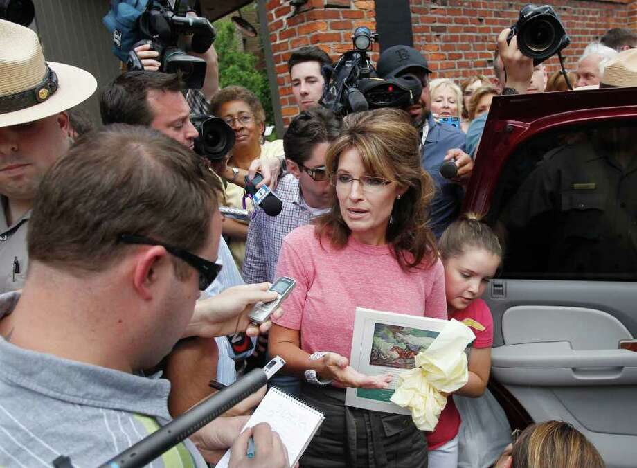 Former Alaska Gov. Sarah Palin, accompanied by her youngest daughter Piper, right, speaks briefly with the media as she tours Boston's North End neighborhood, Thursday,  June 2, 2011. Photo: Steven Senne, AP / AP