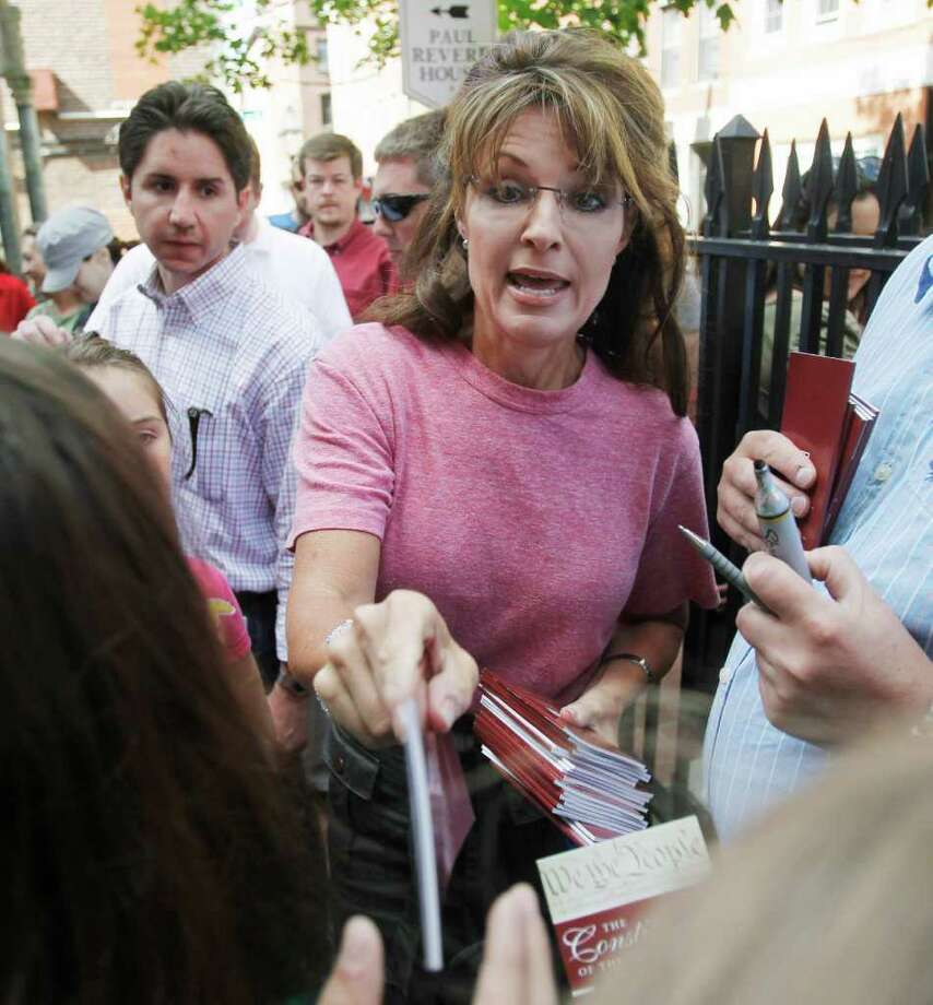 Former Alaska Gov. Sarah Palin hands autographed copies of the U.S. Constitution to tourists during her visit to Boston's North End neighborhood, Thursday, June 2, 2011. Photo: Steven Senne, AP / AP