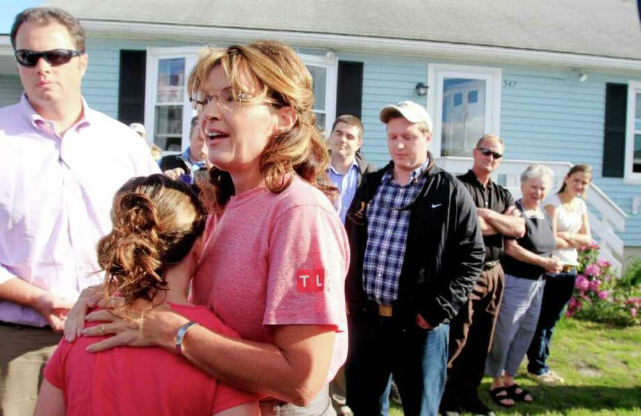 Former Alaska governor and vice presidential candidate Sarah Palin talks with reporters as she arrives at a house party, Thursday, June 2, 2011, in Seabrook, N.H. Photo: Jim Cole, AP / AP