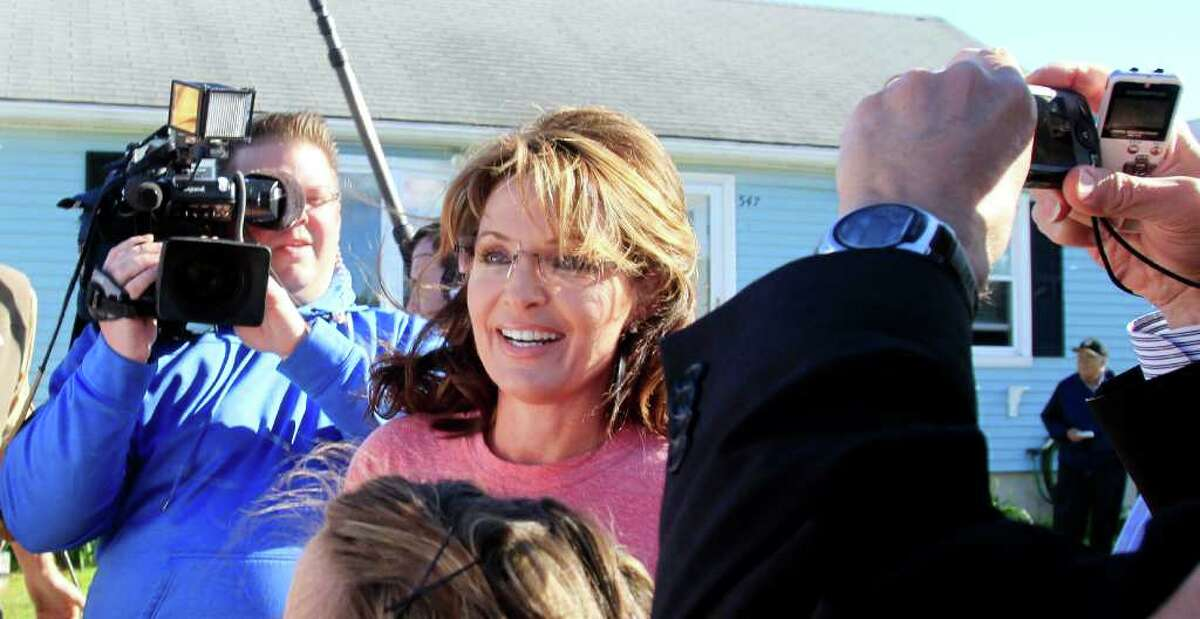 Former Alaska Gov. Sarah Palin talks with reporters as she arrives at a house party, Thursday, June 2, 2011 in Seabrook, N.H.