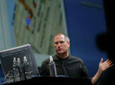 Apple Computer Chairman Steve Jobs demonstrates several new features of the MAC OSX 10.2, or Jaguar system works during his keynote address Wednesday, July 17, 2002, at Macworld in New York.  Jobs made several annoucements including the introduction of Apple's operating system and that it will be shipping out it's popular iPod MP3 player for Windows users in late August. Photo: BETH A. KEISER, AP / AP