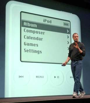 "Apple Computer Inc. chief executive Steve Jobs gestures as he introduces the new iPod during Apple's launch of their new online ""Music Store"" in San Francisco, Monday, April 28, 2003. Photo: AP / AP"