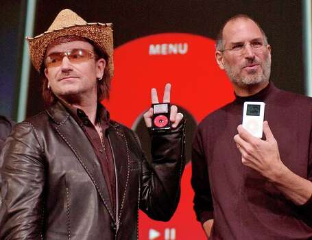 Bono, left, of the band U-2, and Apple Computers Inc. Chief Executive Steve Jobs, right, hold up Apple iPods at an unveiling of a new branded iPod in San Jose, Calif., Tuesday, Oct. 2, 2004.  Bono is holding up a new iPod with a red dial and black casing. Photo: PAUL SAKUMA, AP / AP