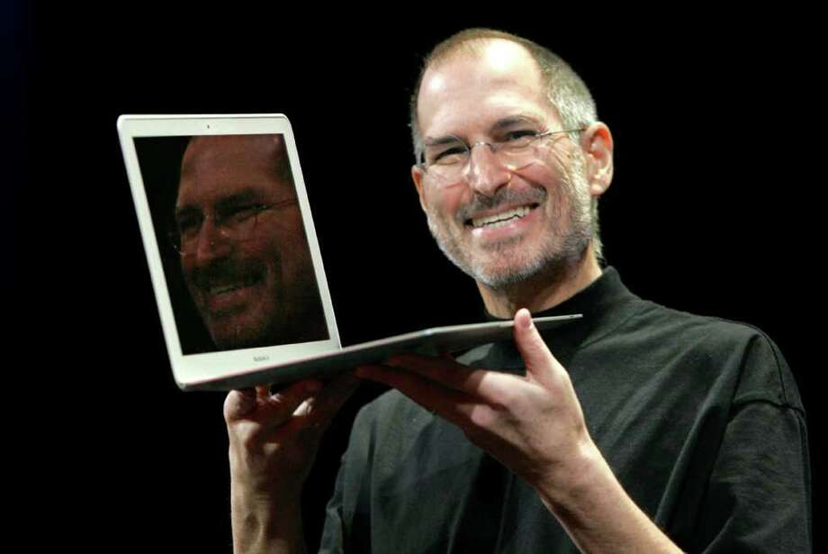 Apple CEO Steve Jobs holds up the new MacBook Air while giving the keynote address at Apple MacWorld Conference in San Francisco, Tuesday, Jan. 15, 2008. The super-slim new laptop is less than an inch thick and turns on the moment it's opened. Photo: Jeff Chiu, AP / AP