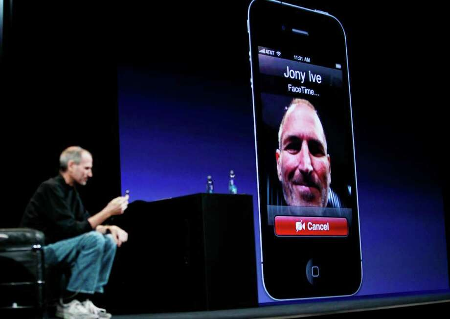 In this file photo made June 7, 2010, Apple CEO Steve Jobs, left, demonstrates the FaceTime feature on the iPhone 4 during the Apple Worldwide Developers Conference in San Francisco. Photo: Paul Sakuma, AP / AP