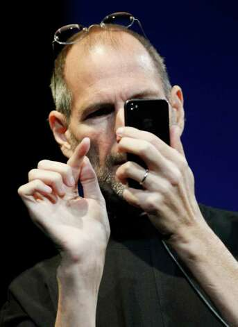 "In this June 7, 2010 photo, Apple CEO Steve Jobs uses the new iPhone 4, at the Apple Worldwide Developers Conference in San Francisco. Apple said Friday, July 2, it is ""stunned"" to find that its latest iPhone model uses a ""completely wrong"" formula to show how many bars of signal strength it's getting. Photo: Paul Sakuma, AP / AP"
