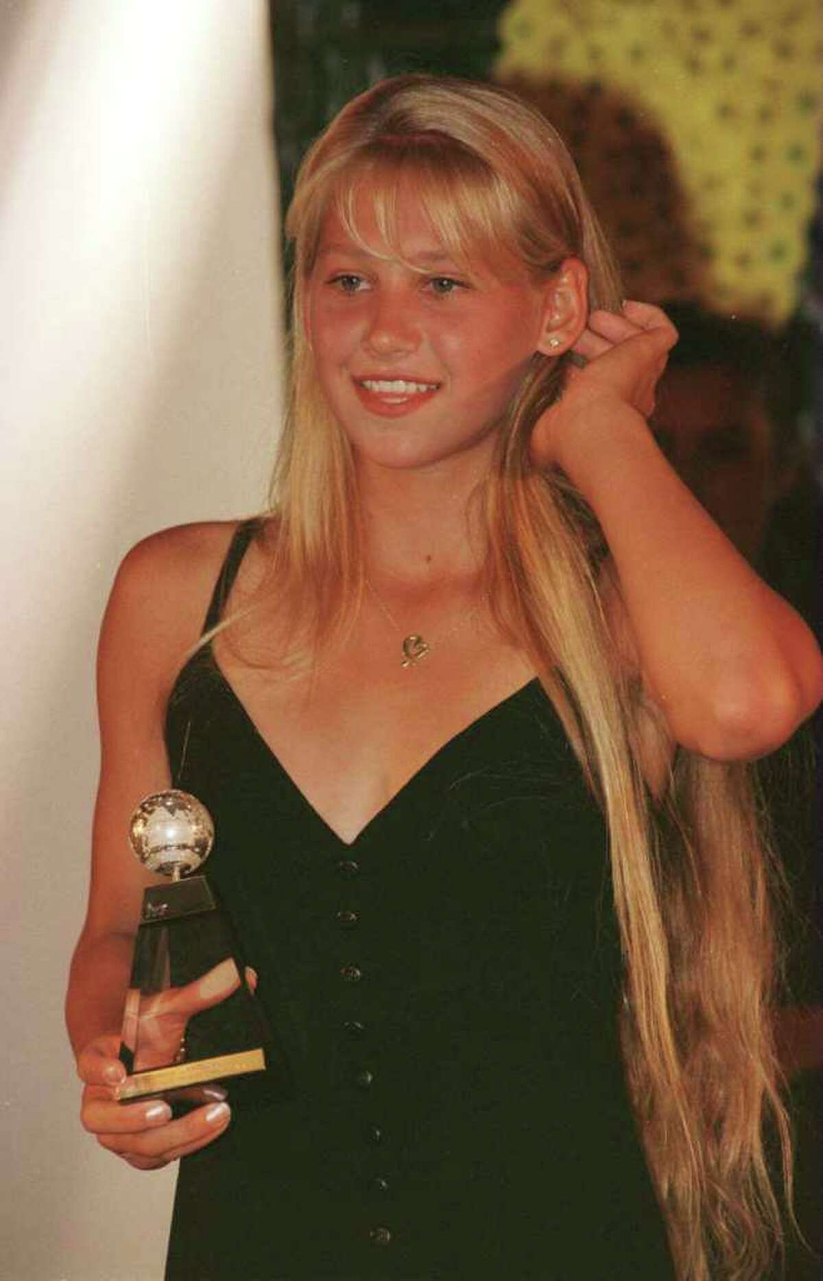 At age 14, Kournikova became the youngest player ever to win a Fed Cup match, then went on to win the European Championships, the Italian Open Junior tournament and the Junior Orange Bowl, earning her the title of ITF Junior World Champion in 1995. Here, she holds that trophy on June 4, 1996, during the ITF World champions dinner at the 1996 French Open at Roland Garros in Paris, France. She turned pro in 1995 and, in 1996, won of the Sanex WTA Tour Most Impressive Newcomer Award.