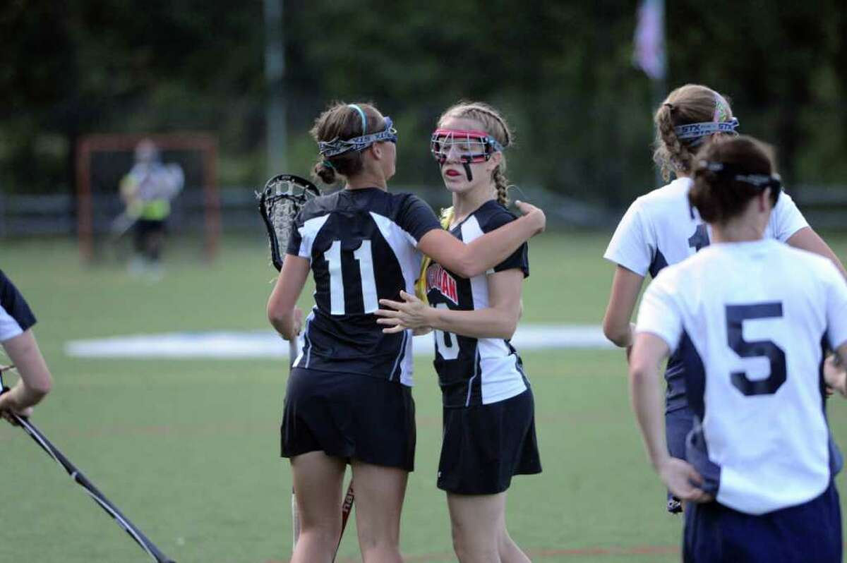 New Canaan's Elizabeth DeTour, left, and Sarah Mannelly celebrate Manelly's goal as Wilton High School hosts New Canaan in a girls Class M quarterfinals lacrosse game in Wilton, Conn., June 3, 2011.