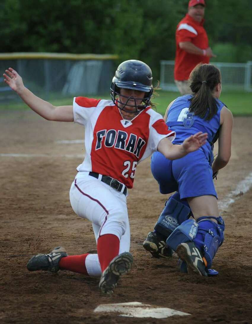 Foran's Jamie Healey slides safely into home around Darien catcher Olivia Gozdz in the fifth inning their Class L semifinal game at DeLuca Field in Stratford on Monday, June 6, 2011. Foran won the game 4-1.