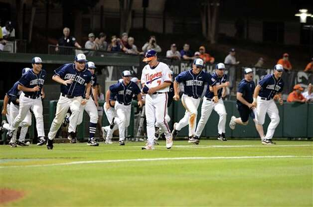 Clemson head coach Jack Leggett leaves the field after his team lost  to Connecticut 14-1, while the Huskies swarm  after an NCAA college baseball regional tournament game at Doug Kingsmore Stadium Monday, June 6, 2011, in Clemson, S.C. (AP Photo/ Richard Shiro) Photo: AP