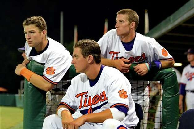 Clemson players Spencer Kieboom, left, Jon McGibbon, center, and Brad Miller watch during their 14-1 loss to Connecticut during an NCAA college baseball regional tournament game  at Doug Kingsmore Stadium Monday, June 6, 2011, in Clemson, S.C. (AP Photo/ Richard Shiro) Photo: AP