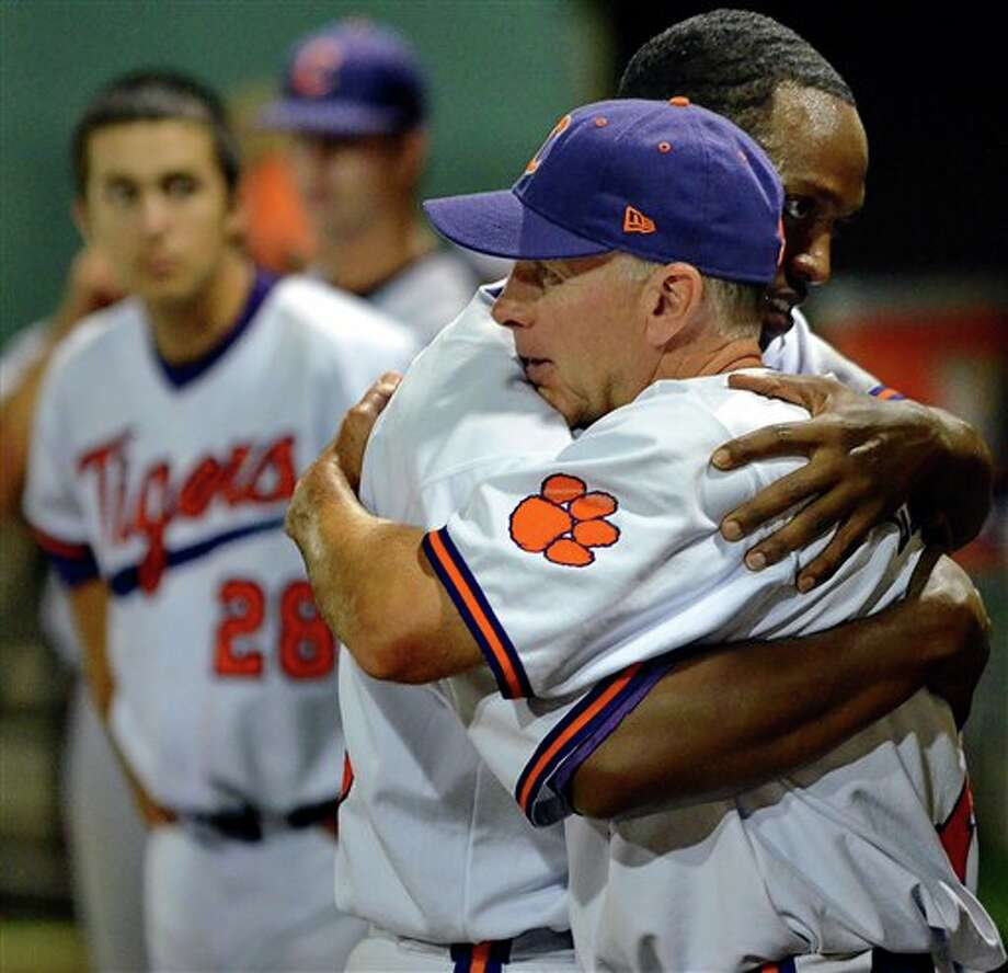 Clemson head coach Jack Leggett, front,  hugs Chris  Epps while Jonathan Meyer (28) looks on after losing to Connecticut 14-1 at an NCAA college baseball regional tournament game against at Doug Kingsmore Stadium Monday, June 6, 2011, in Clemson, S.C. (AP Photo/ Richard Shiro) Photo: AP