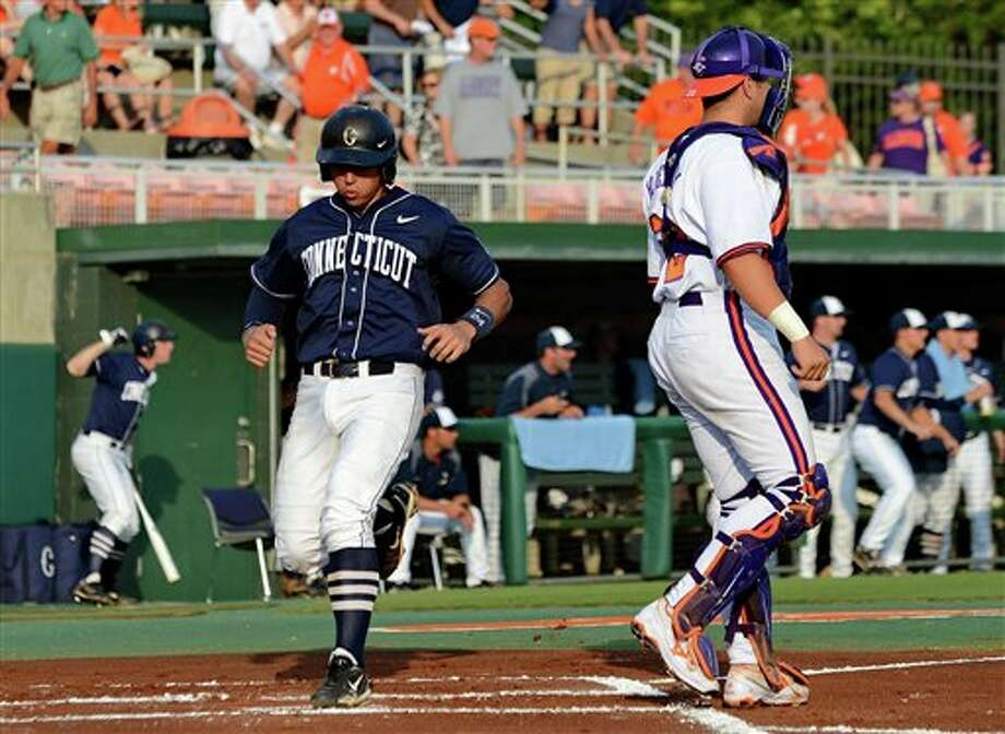 Connecticut's  L.J. Mazzilli, keft. scores behind Clemson catcher Spencer Kieboom, right, during an NCAA college baseball regional tournament game at Doug Kingsmore Stadium Monday, June 6, 2011, in Clemson, S.C. (AP Photo/ Richard Shiro) Photo: AP