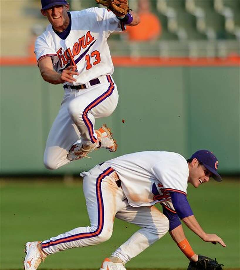 Clemson short stop Brad Miller (13) jumps over second baseman Jason Stolz after completing a throw to first during an NCAA college baseball regional tournament game against Connecticut at Doug Kingsmore Stadium Monday, June 6, 2011, in Clemson, S.C. (AP Photo/ Richard Shiro) Photo: AP