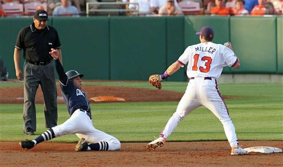 Clemson shortstop Brad Miller (13) gets the force out on Connecticut runner George Springer, center, at second base as umpire Kelly Gonzales looks on during their NCAA regional college baseball game on Monday, June, 6, 2011 at Doug Kingsmore Stadium in Clemson, S.C. (AP Photo/Anderson Independent-Mail, Mark Crammer) Photo: AP