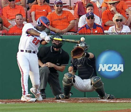 Clemson's Chris Epps, left, hits a single as catcher Doug Elliot, right, and home plate umpire Jim Garman look on during their NCAA regional college baseball game on Monday, June, 6, 2011 at Doug Kingsmore Stadium in Clemson, S.C. (AP Photo/Anderson Independent-Mail, Mark Crammer) Photo: AP