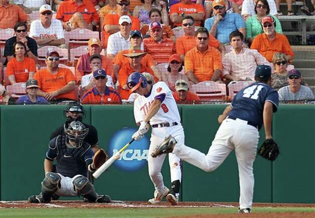 Clemson's Richie Shaffer, center, hits a solo home run off of Connecticut pitcher Greg Nappo (41) as catcher Doug Elliot and home plate umpire Jim Garman look on during their NCAA regional college baseball game on Monday, June, 6, 2011 at Doug Kingsmore Stadium in Clemson, S.C. (AP Photo/Anderson Independent-Mail, Mark Crammer) Photo: AP