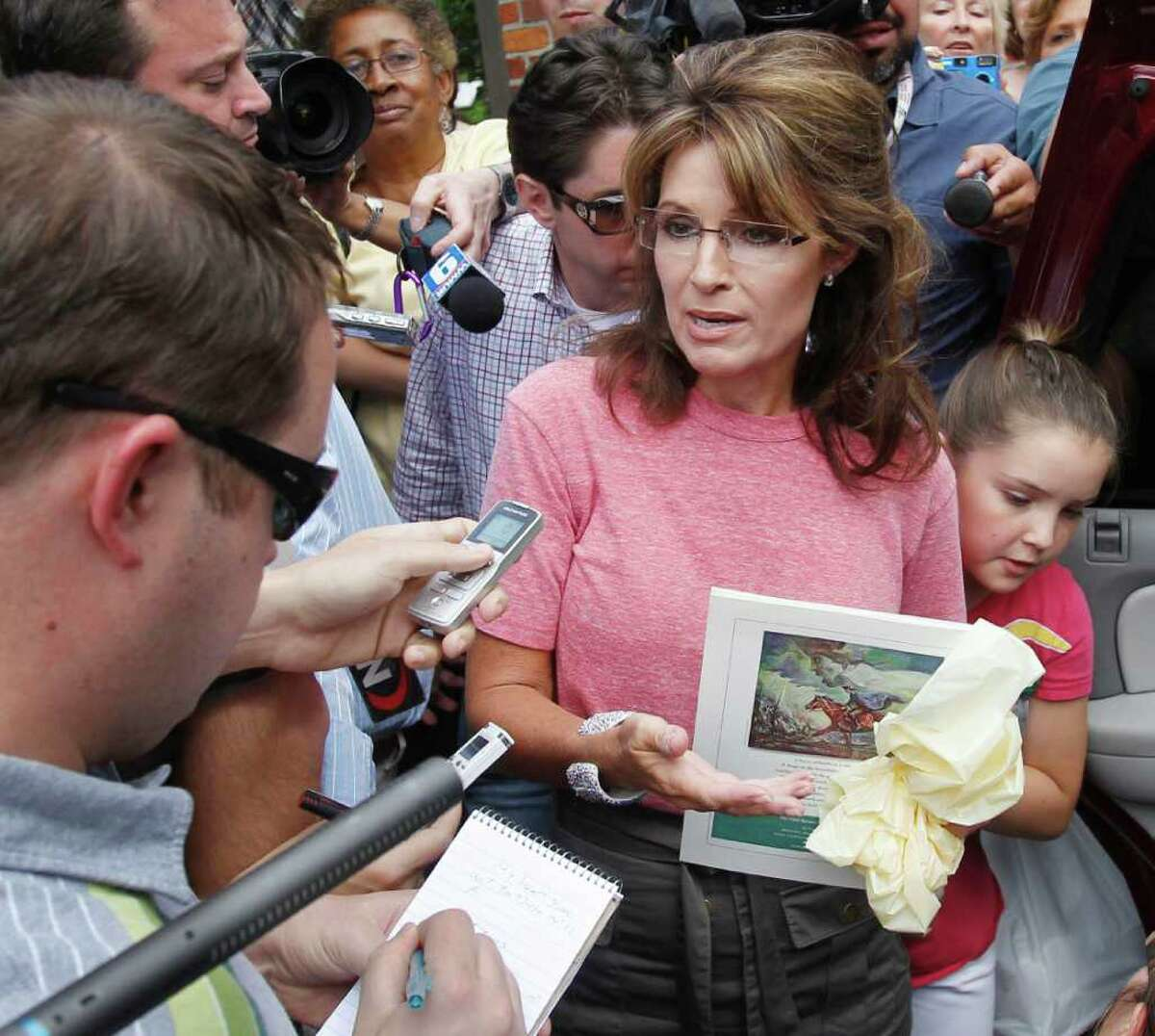 FILE - In this June 2, 2011, file photo former Alaska Gov. Sarah Palin, holding a booklet depicting Paul Revere, speaks briefly with the media as she tours Boston's North End neighborhood. On Fox News Sunday Palin insisted Sunday, June 5, 2011 in Washington that history was on her side when she claimed that Paul Revere's famous Massachusetts ride was intended to warn both British soldiers and his fellow colonists. At right is Palin's daughter Piper. (AP Photo/Steven Senne, File)