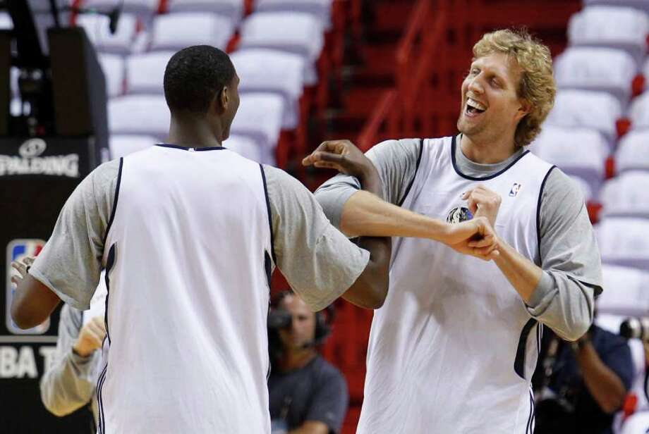 Dallas Mavericks' Ian Mahinmi, left, and Dirk Nowitzki chat as they warm up during a practice session in Miami, Monday, May 30, 2011. The Miami Heat will play the Mavericks in Game 1 of the NBA basketball finals on Tuesday. Photo: Wilfredo Lee/Associated Press