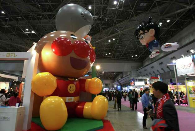 Giant figures of Anpanman, left, and Top Detective Conan, right in the air, popular Japanese anime cartoon series characters, greet visitors during the business day of the Tokyo International Anime Fair 2010 in Tokyo, Japan, Thursday, March 25, 2010. More than 200 anime-related companies and organizations gathered in this annual event. Photo: Koji Sasahara, AP / AP