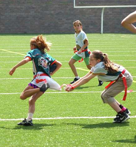 "Nicole Maloney makes a ""tackle,"" pulling the flag as Michelle Morganti prepares to back her up. Photo: Contributed Photo / Greenwich Citizen"