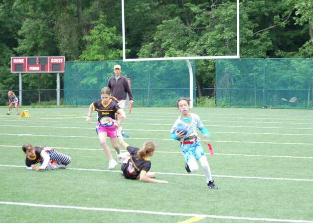 Katie Large fakes out the defense as she heads for a touchdown. Photo: Contributed Photo / Greenwich Citizen