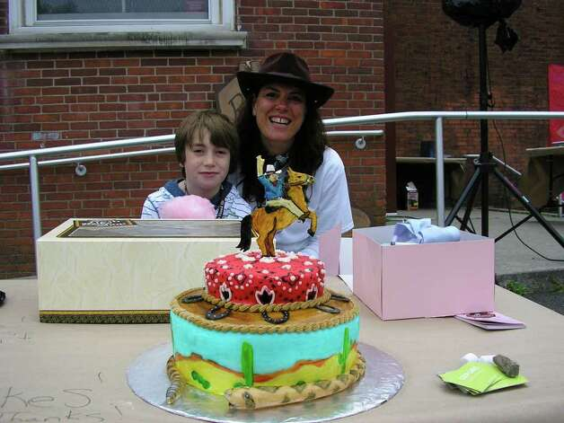 Cake walk emcee Beth Cherico and her fourth-grade son James show off one of the cakes donated as a prize. Every 15 minutes fair-goers walked around in a circle and the person left standing on the winning spot when the music stopped walked away with a frosted delight. Photo: Contributed Photo / Darien News